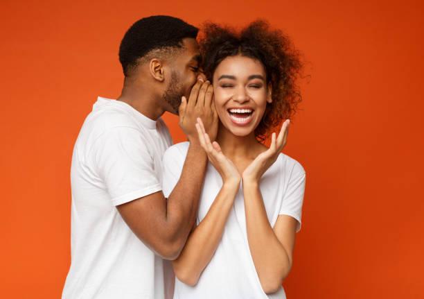 zwarte man geheim delen met zijn vriendin - fluisteren stockfoto's en -beelden