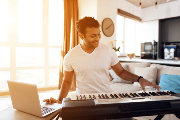 A black man sits in the living room of his apartment and plays a synthesizer. He composes music. stock photo