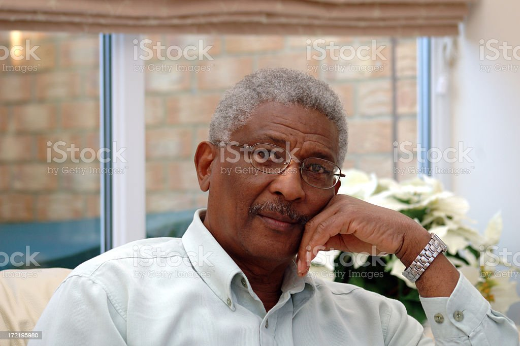 Black man sitting pensively in room royalty-free stock photo