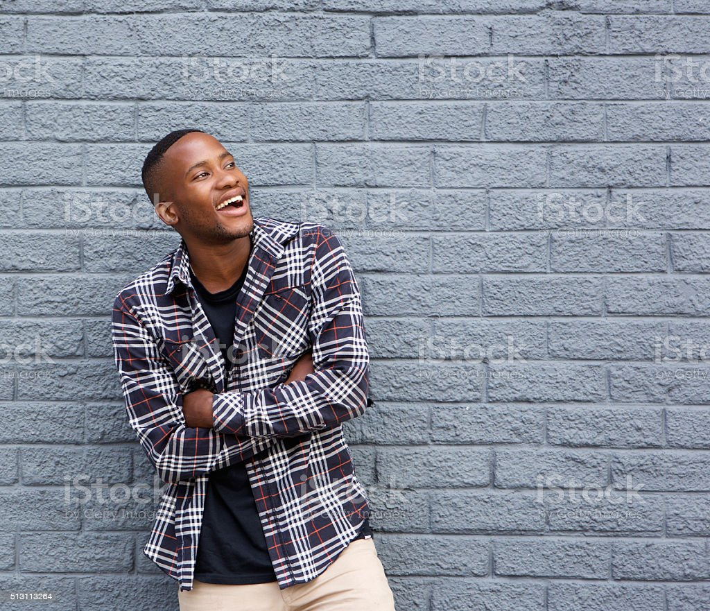 Black man smiling with arms crossed against gray wall stock photo