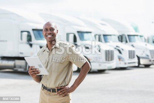 istock Black man standing in front of semi-trucks 856730386