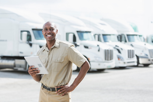 An African-American man in his 30s standing in front of a row of parked semi-trucks outside a distribution warehouse, holding a digital tablet.
