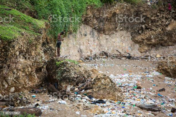 Dominican Republic, Santo Domingo - September 7, 2017: a lot of plastic and various garbage on the coast of the sea, wave washes away trash. Man pollutes the environment. Pure planet, save the planet. Third world country