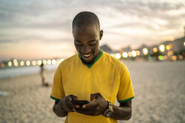 Black man typing a message at the beach Black man typing a message at the beach brazilian ethnicity stock pictures, royalty-free photos & images