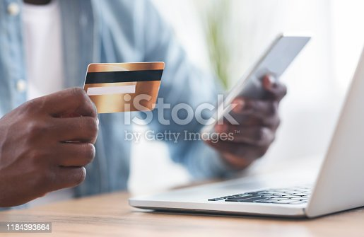 1173546354 istock photo Black man using card and smartphone for paying bills online 1184393664