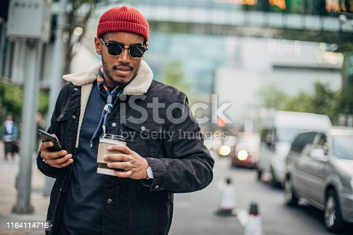 One man, handsome black guy on coffee break downtown, using smart phone.