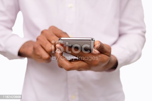 950613878 istock photo Black man using smartphone, browsing social media over white background 1182420958