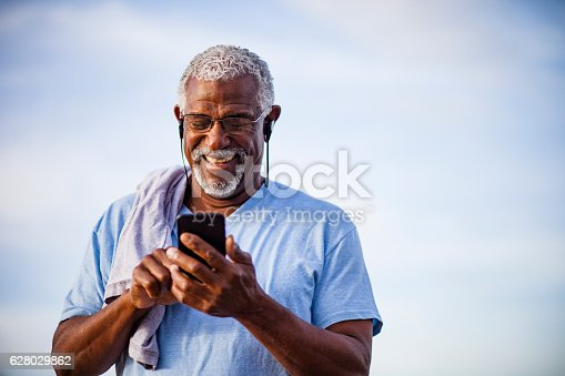 An attractive senior black man uses his smartphone on the trail