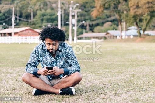 Black man using smartphone outdoors
