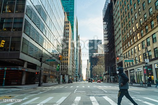 New York, NY, USA - April 6, 2020: A black man wearing protective mask man crossing 6th Avenue of Americas in Midtown Manhattan deserted because of the city lockdown caused by COVID-19 pandemic.