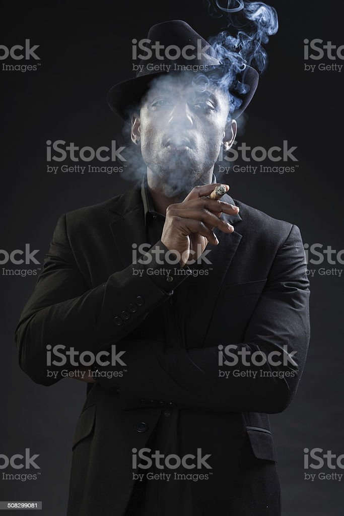 Black man wearing suit and hat gangster style smoking cigar. stock photo