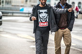 Geneva, Switzerland  - May 13, 2014: Black man wearing t-shirt with President Obama portrait, walking with another man and talking, pointing to something on Geneva street