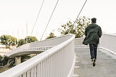 view from behind attractive young black african man with cool casual wear running on a modern bridge in the city, lifestyle concept