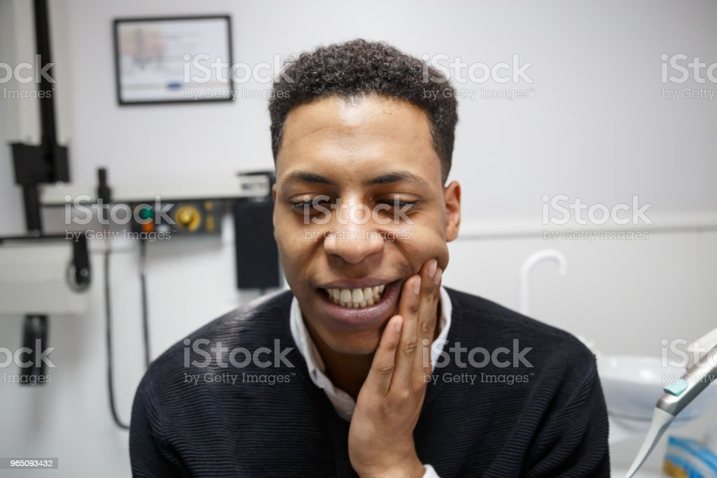 Black man with toothache in cabinet royalty-free stock photo