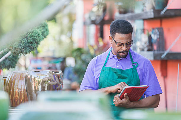 schwarzer mann arbeitet im garten-center mit digitaltablett - einzelhandelsarbeiter stock-fotos und bilder
