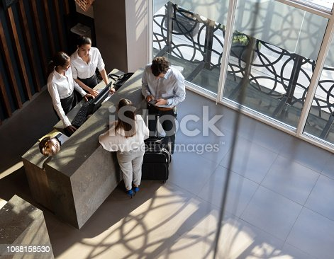 istock Black manager and recepcionist checking in a couple and man looking at his smartphone 1068158530