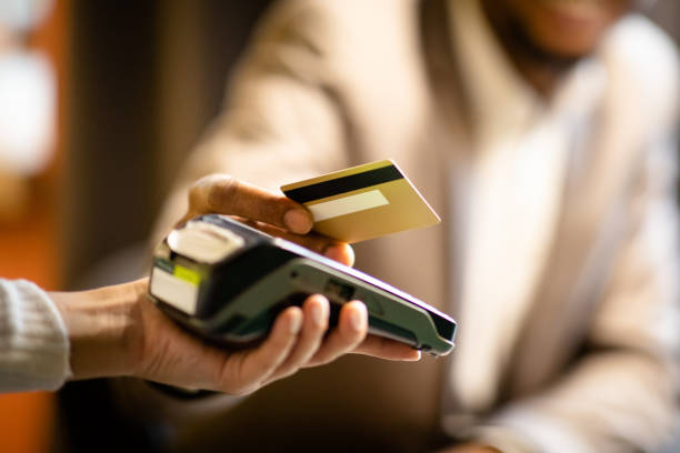 black manager giving credit card to waitress - paying with card contactless imagens e fotografias de stock