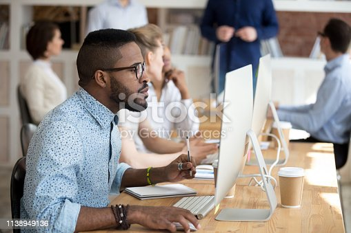 958531418 istock photo Black manager holding pen make notes on textbook using pc 1138949136