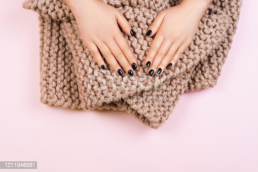 946930880 istock photo Black manicure with cozy wool knitted scarf on pastel background. 1211046351
