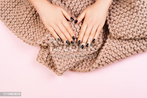 946930880 istock photo Black manicure with cozy wool knitted scarf on pastel background. 1213960828