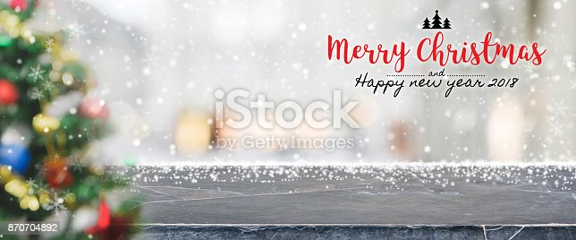 530427918 istock photo Black marble stone table top on blur with bokeh christmas tree background with snowfall - can be used for display or montage your products. 870704892