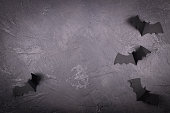 Black marble surface with paper bats. creepy holiday background with space for text