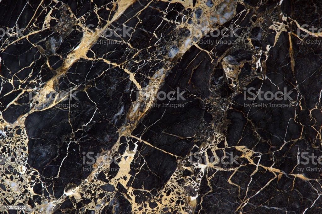 Black marble with beautiful yellow streaks, called New Portoro Black marble with beautiful yellow streaks, called New Portoro. Abstract Stock Photo