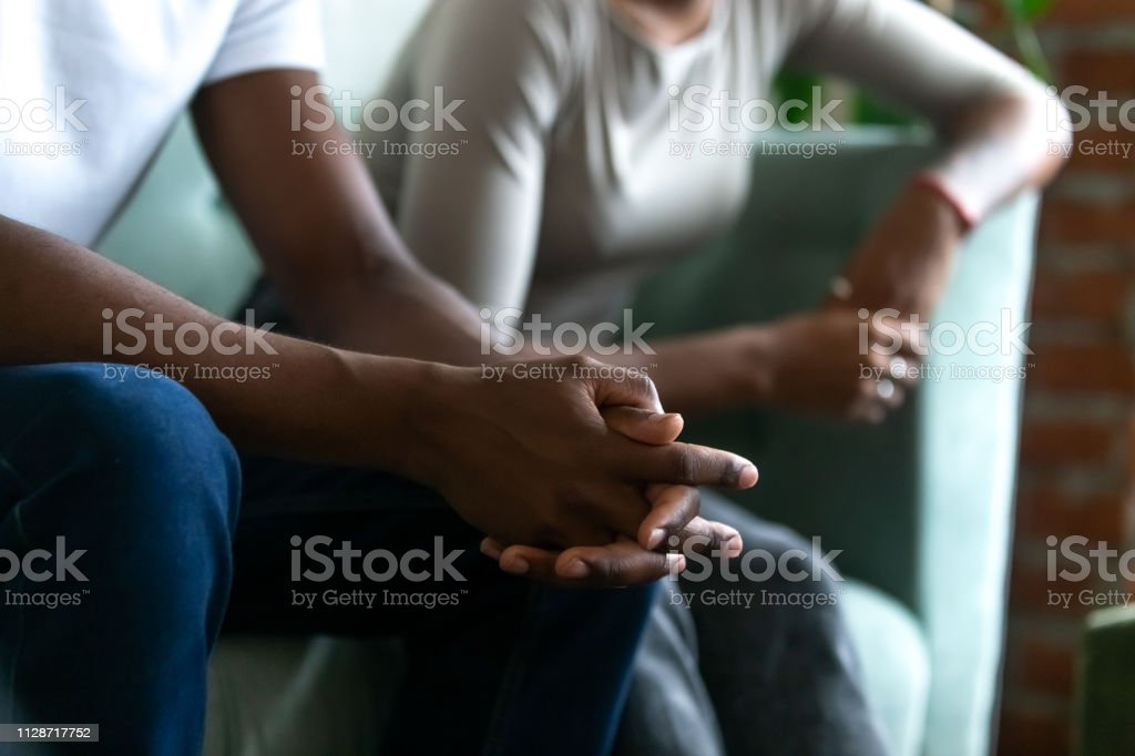 Black married couple spouses quarrelled close up male hands Black married couple spouses quarrelled sitting separately on couch, close up focus on husband body part folding hands together. Break up and divorce, misunderstanding and split in relations concept Adult Stock Photo