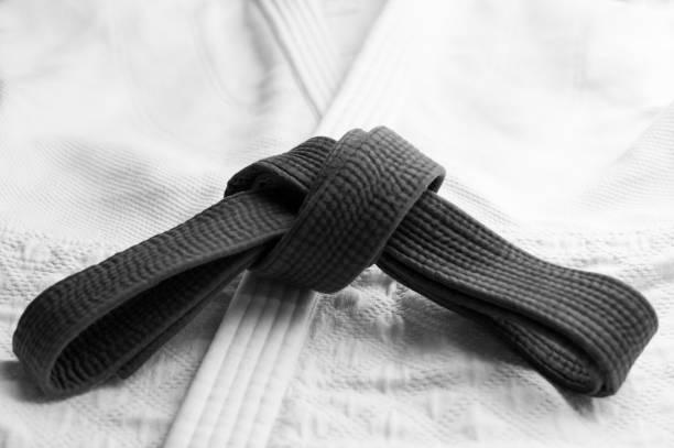 Black martial arts belt with white kimono in background stock photo