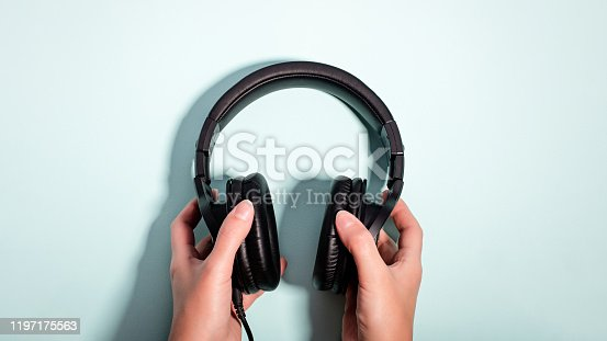 Black massive headphones in female hand on pastel background, copy space. Modern technology flat lay with over-ear earphones in woman hand, modern lifestyle concept, top view