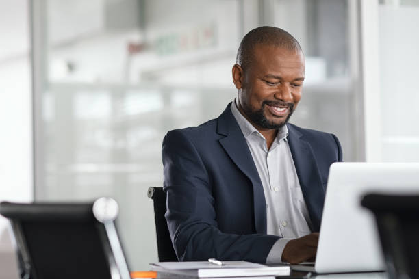 Black mature businessman working on laptop Positive mature businessman working on laptop in modern office. Successful african business man working on computer while sitting at desk. Smiling middle aged man working in a corporate. using computer stock pictures, royalty-free photos & images