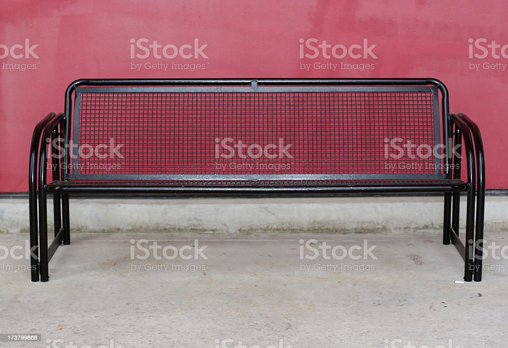 Black Metal Bench Against a Red Wall royalty-free stock photo