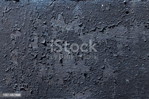 Texture of black coloured metal background with a peeling cracked layers of paint.