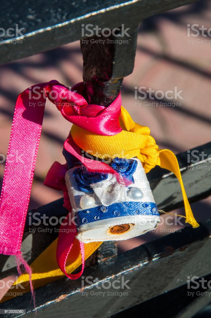 A black metal fence with bright ribbons and wedding padlocks stock photo