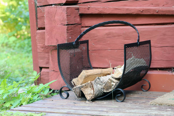 Black Metal Firewood Holder Loaded with Firewood for Sauna in Finland stock photo