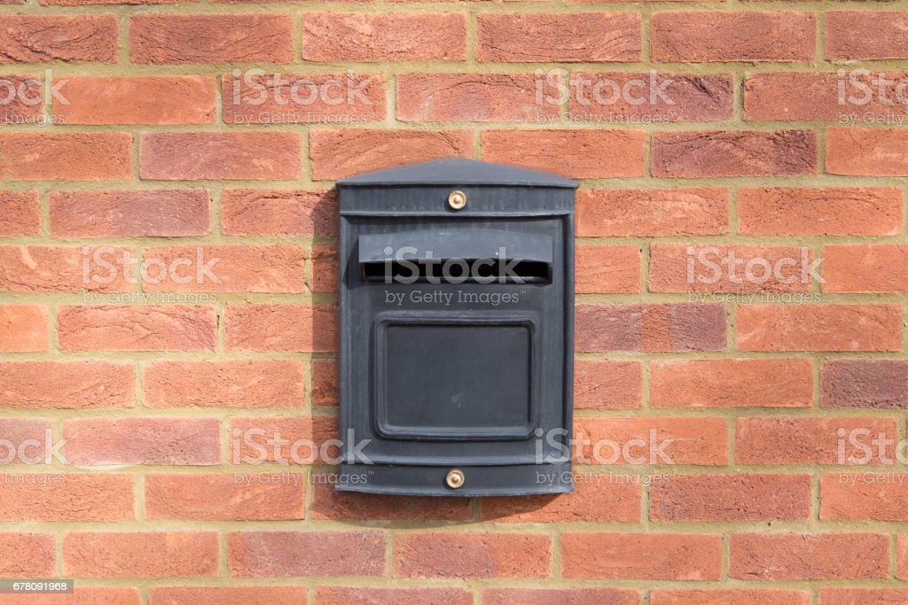 black metal letter box on red brick wall stock photo