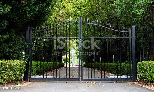 Black metal wrought iron driveway property entrance gates with lush green hedge and garden trees