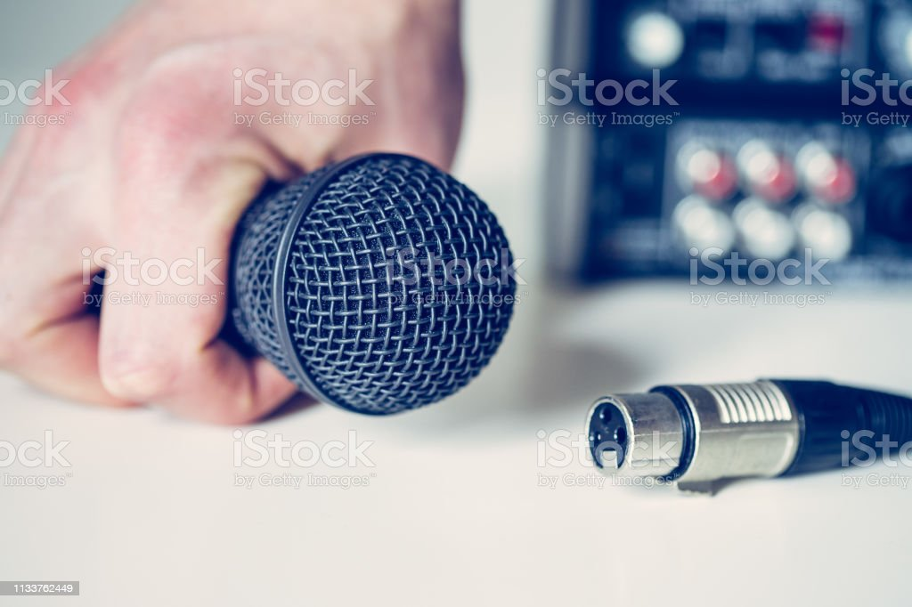 Close up picture of holding in hand microphone and audio cable, mixer...
