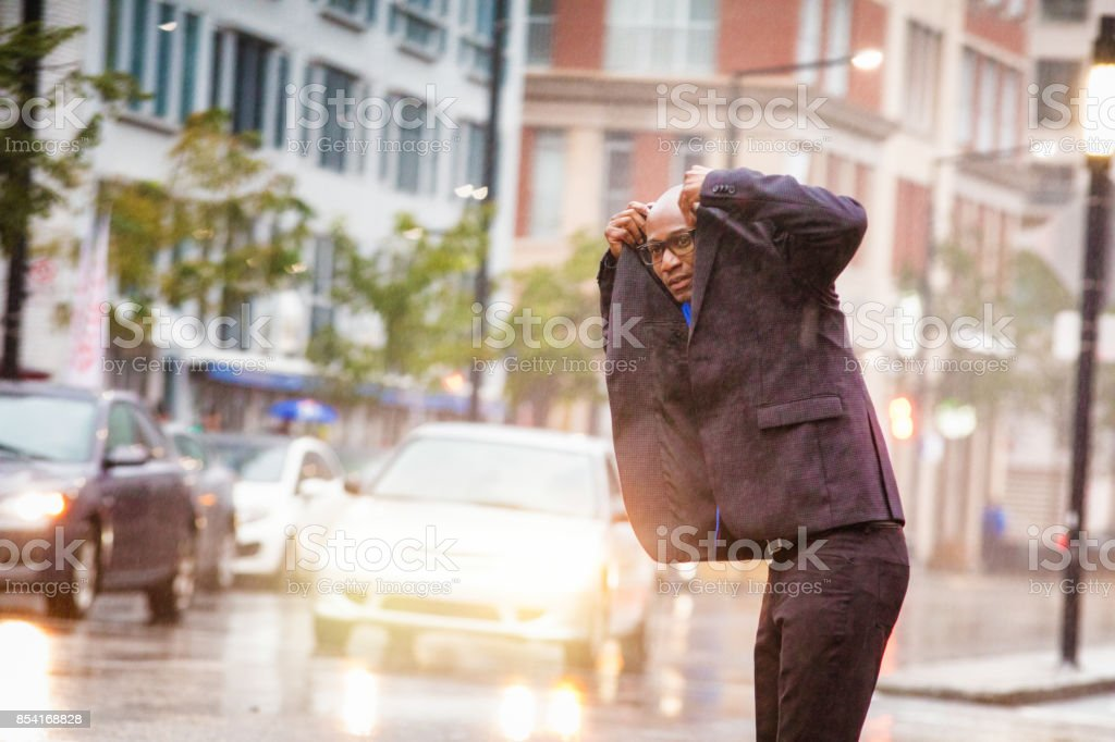 Black mid adult businessman anxiously waits for ride in rainstorm stock photo