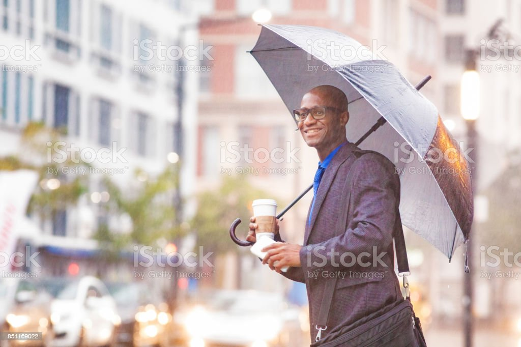 Black mid adult businessman smiling as his rideshare approaches in rainstorm stock photo