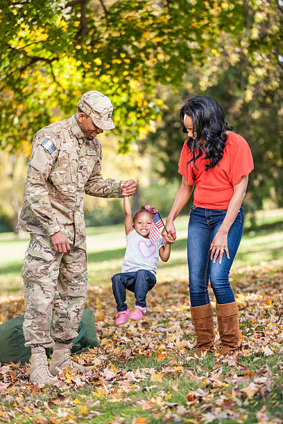 Black Military Family Playing in Park stock photo