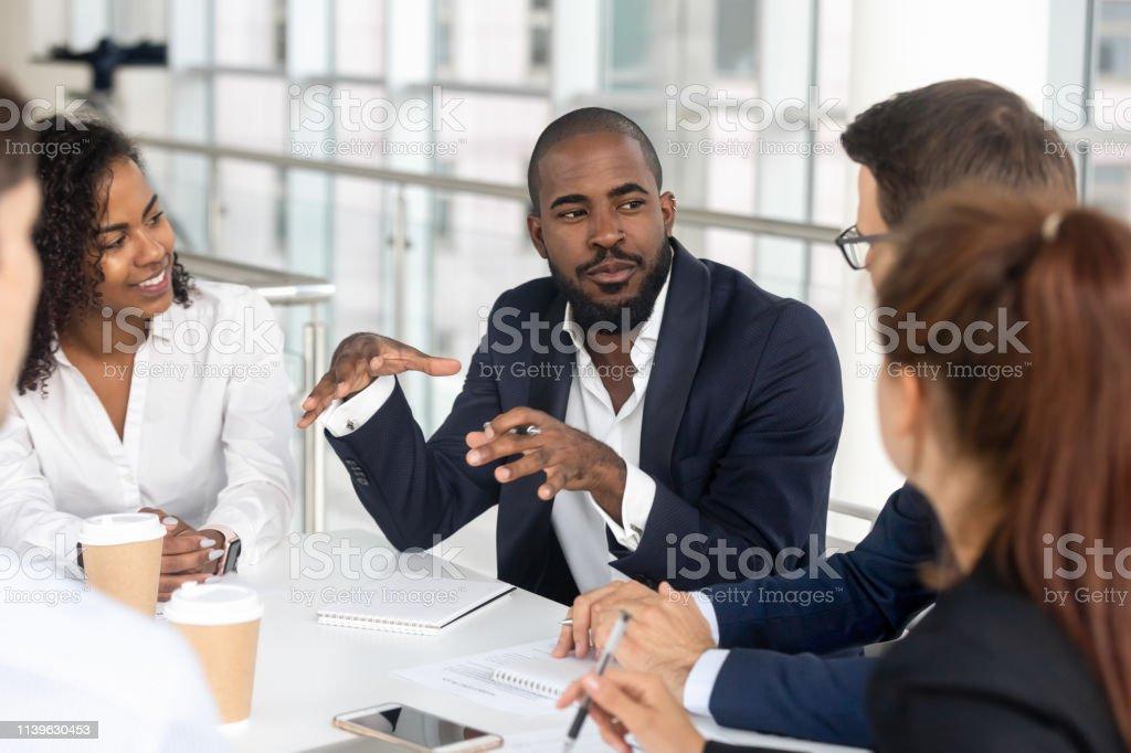 Black tusenåriga Boss ledande företags grupp under Briefing i styrelse rummet - Royaltyfri Affärskvinna Bildbanksbilder