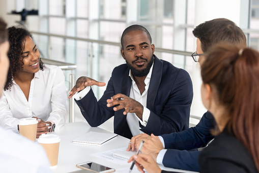 istock Black millennial boss leading corporate team during briefing in boardroom 1139630453