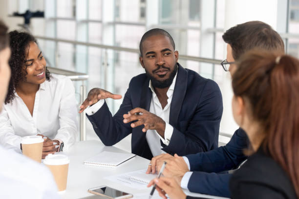 black millennial boss leading corporate team during briefing in boardroom - leadership stock pictures, royalty-free photos & images