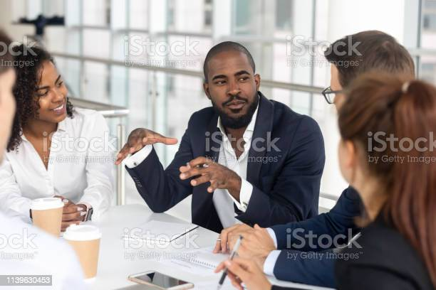 Black Millennial Boss Leading Corporate Team During Briefing In Boardroom Stock Photo - Download Image Now