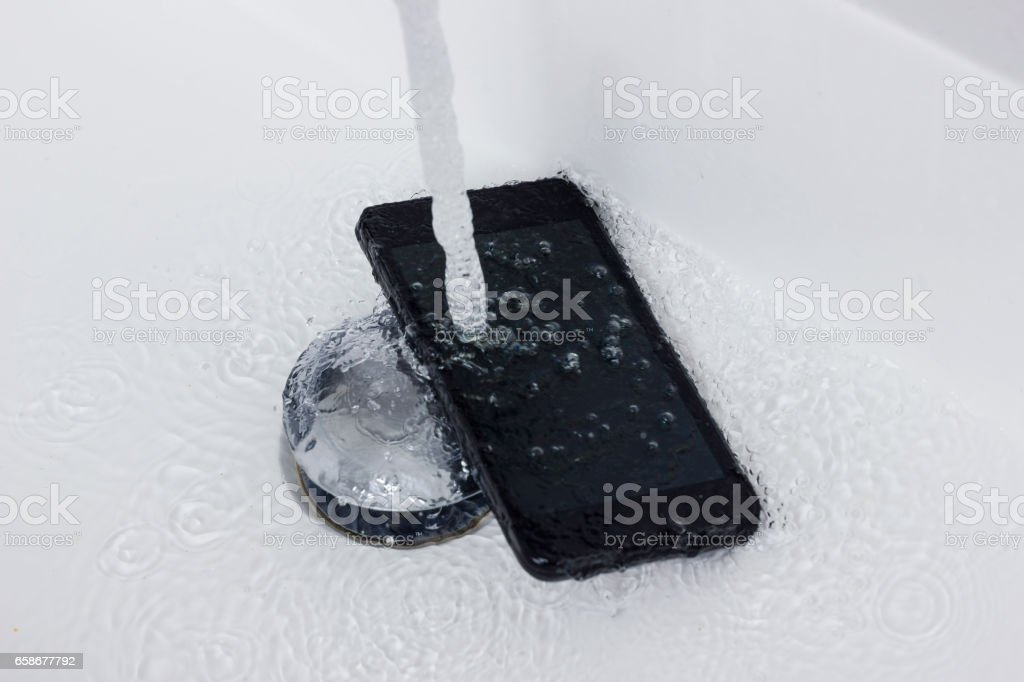 black mobile phone falling into washbasin flowing with water jet stock photo