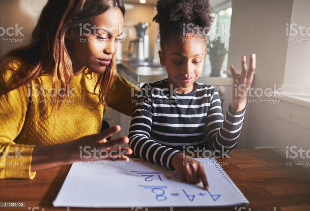 Black mom and child doing homework stock photo