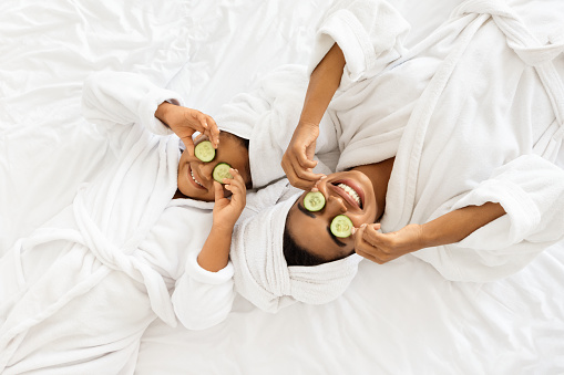 Beauty Spa Day. Cheerful Black Mom And Daughter In Bathrobes Lying With Cucumber Slices On Eyes, Doing Face Mask Treatment, Wearing Towel On Head, Having Fun Together At Home, Top View With Copy Space