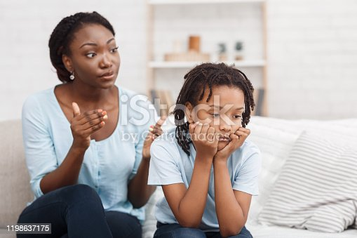 Family Conflict. Quarrel between black mother and daughter at home, sulky child ignoring her mom, copy space