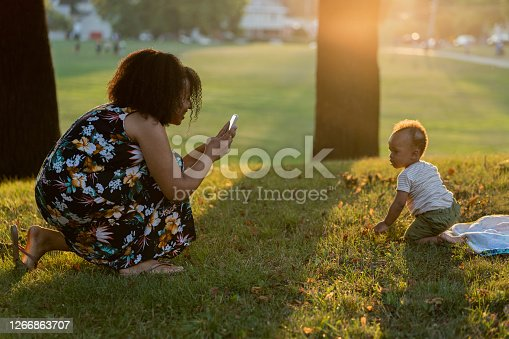 Black mom talking photos of her baby in the park